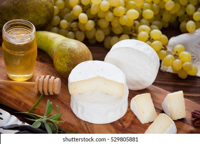 Camembert cheese on a wooden board with honey, fruits and nuts
