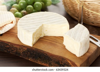 camembert cheese on wooden board with knife, wineglass bread basket and grapes in background