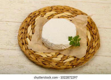 Camembert cheese with parsley over the wooden background