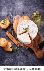 Camembert cheese with rosemary on wooden board. Selective focus