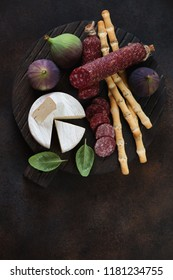 Camembert cheese, salami, grissini and ripe figs, flatlay over dark brown metal background, vertical shot with copyspace