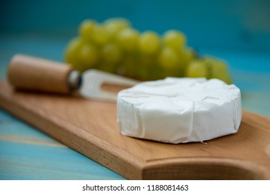 camembert, with a fork for cheese and grape on a cutting board, on a blue wooden background