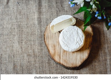 Camembert French soft cheese with white mold on a wooden board. Sliced round cream cheese camembert, on a textile background from a sackcloth. Top view.  copyspace