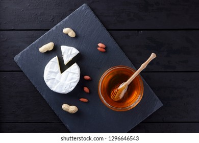 Camembert and honey on a black slate board. Soft cheese with mold and peanuts on a black background. Cheese and nuts on a stone board. Copy space