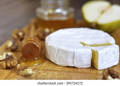 Camembert with honey,walnuts and pear on an old wooden background.