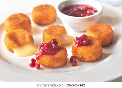 Camembert nuggets with cranberry sauce on the white plate
