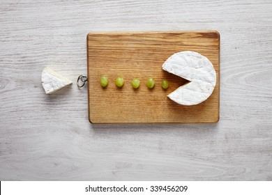 Camembert, soft cheese, cut out like pacman eating green grapes