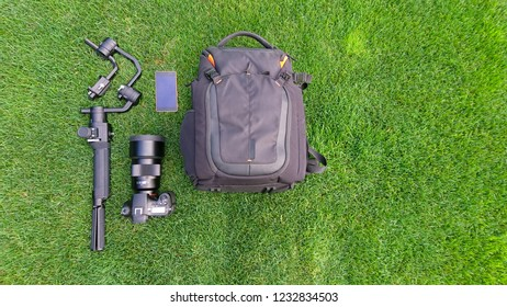 A camera, bag, gimbal, smart phone and video production equipment flat lay on a lush grass, turf background.