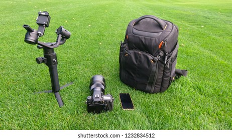 A camera, bag, gimbal, smart phone and video production equipment set up on a lush grass, turf background.