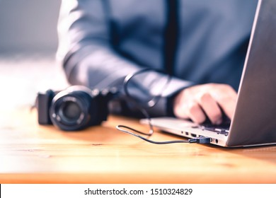 Camera connected to laptop with usb cable. Man editing photos with computer software. Photographer transfer files to computer from DSLR. Backup storage for images. Professional editor working.