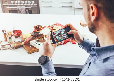 camera eats first concept: man taking pictures with his phone of the food on the table. social media life concept