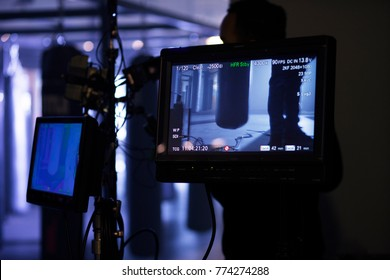Camera gear monitor with punching bags in misty cinematic boxing gym and film set. Behind the scenes shot.