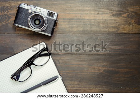 Camera, glasses and notepad on wood