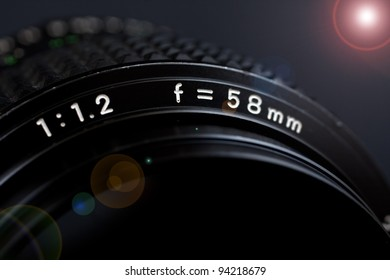 camera lens 58mm 1.2 closeup with flare on black background