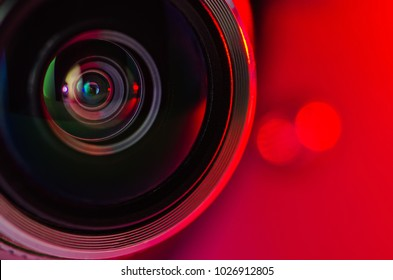 The camera lens and the beautiful light red color . Horizontal photo