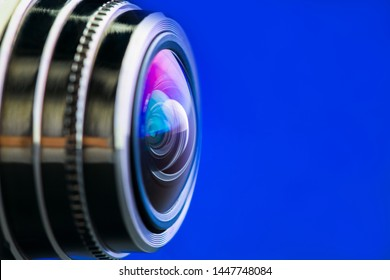 Camera lens with blue backlight. Side view of the lens of camera on blue background. Blue camera Lens close Up.