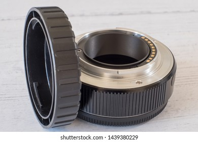 camera lens extension tube and camera lens end cap on with painted board surface.