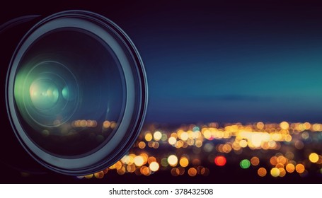 The camera lens on the background blurry city lights.