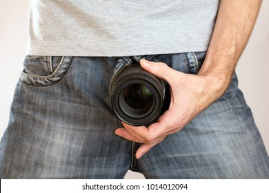 camera lens out of jeans like mens penis. Potency sexual problems and pornography concept. Man with camera lens near pants gray t-shirt. close up, selective focus