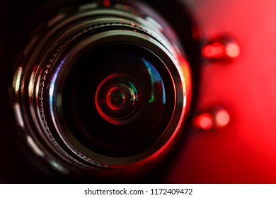 Camera lens and red backlight . Horizontal photography