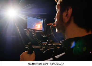 Camera man filming music video clip on camera with playback screen on in bright back light