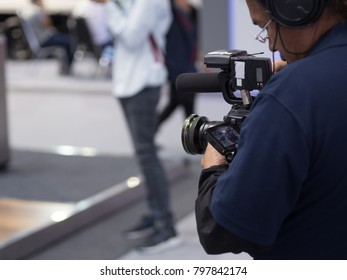 Camera Man using professional camcorder filming video in the conference