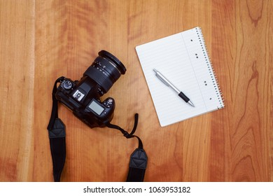 camera, notepad with pen and coffee on wooden table from above