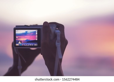 Camera on hand taking a picture of beautiful sunset in red island beach, banyuwangi, indonesia, nearby of bali island