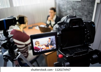 camera on the set of a business meeting between a man and a woman