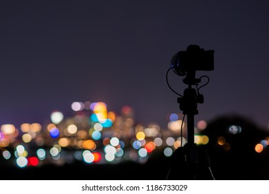 Camera on tripod with blurred bokeh city lights in background.