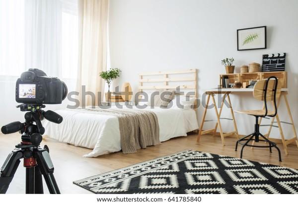 Camera on a tripod in modern bedroom interior