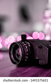 The camera on a wooden background, retro photo. Pink tint photo