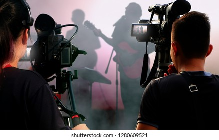 Camera operators working with video equipment at indoor live concert