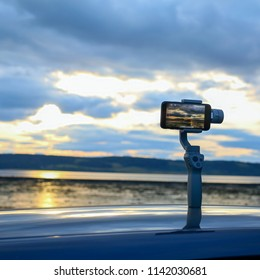 camera osmo and smartphone shoots a timelapse video of the sunset on the ocean. innovative technologies. travel and entertainment