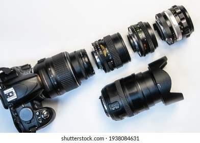 camera and photo lenses on white background. Concept of interchangeable lenses and optics. Flat lay, top view.
