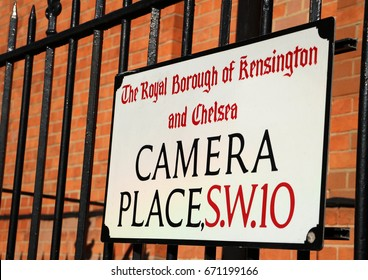 Camera Place: Colour photograph of street sign against red brick wall with black railings, in Chelsea, London.