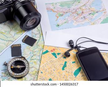 Camera, smartphone with headphones on tourist maps