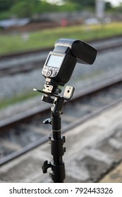 camera speed-light on stand with railway background for external flash on