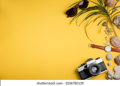 Camera, sunglasses and watches on yellow. Collecting seashells and capturing happy moments. Travel to the coast.