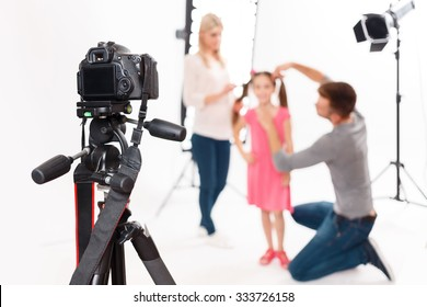 Camera is supported. Photographer leaves his camera fixed safely while helping to prepare little girl for shooting