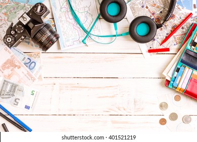 Camera, touristic maps, headphones, wallet with credit cards, phone, colorful pens, euro banknotes and coins on the white desk. Travel background. Journey planning. Tourist essentials. Space for text