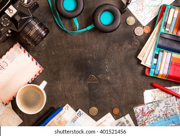 Camera, touristic maps, passport, cup of coffee, headphones, wallet with credit cards, euro banknotes and coins on the black desk. Travel background. Tourist essentials. Plan a journey. Space for text