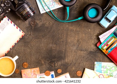 Camera, touristic maps, passport, toy car, coffee, headphones, wallet with credit cards, euro banknotes and coins on a black desk. Travel background. Tourist essentials. Plan a journey. Space for text