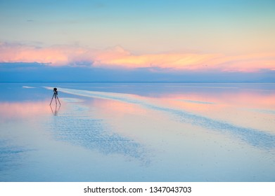 Camera with tripod shooting sunset on Salar De Uyuni salt flat in Bolivia. Travel photography concept