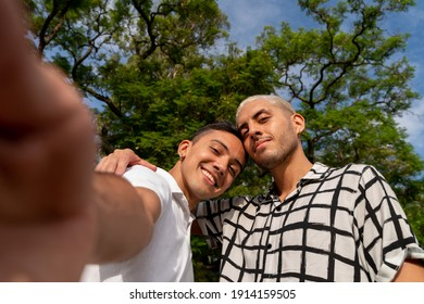 Camera view as young latin american gay couple taking selfies in a public park.