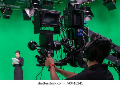 Cameraman and announcer working in a broadcast television virtual green screen studio room.
