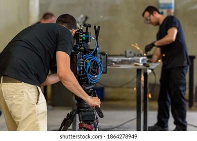 Cameraman with digital film camera in industrial steelworks