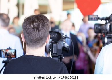 Cameraman filming media event or press conference with a video camera