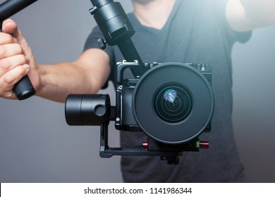 Cameraman holding gimbal with slr camera
