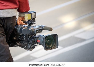 cameraman holding his professional camcorder in the street. Operator in social environment, filming, news outlet, motion-picture cameraman